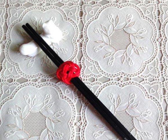 ,筷子环也是一个点睛之笔。宴会桌上的筷子套在一个红红的筷子环里,虽然它只是小小的,静静的放在那,但也为热闹气氛增添一抹古朴和温馨的气氛。  编双环结筷子环需要准备的原料:2根30厘米中国结红绳。  1、我们先取一根长30厘米的红绳,对折后用珠针固定,分为左右两根绳。  2、我们把右边的绳向左顺时针压在左线上。  3、再用左线逆时针做压一挑一,压一挑一,压一出。  4、好,双钱结就编好了,看看,就是这样的。  5、我们领取一根红绳,按照编好的双钱结,沿着红绳的一侧穿入。  6、继续穿,切记,要始终沿着双钱结