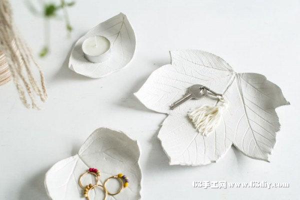 材料:超轻粘土(自然风干的)、叶形完整的大树叶、亚克力压泥辊、工艺小刀、光泽清漆、油漆刷。  1、使用亚克力压泥辊将粘土擀成厚薄均匀的薄片,可稍薄些,这样制作出的粘土叶子会比较精细,薄片的面积需大于树叶。  2、将清洗干净晾干的树叶正面朝上覆盖在粘土薄片上,确保树叶边缘不超出粘土薄片。  3、使用亚克力压泥辊轻轻得、用力均匀的滚压树叶,使每条叶脉都复制到粘土上。  4、小心的揭下树叶。  5、使用工艺小刀沿树叶边缘留下的压痕切割去多余的边缘粘土。   6、小心的提起粘土叶子,将其放入到碗里,使叶子形成与